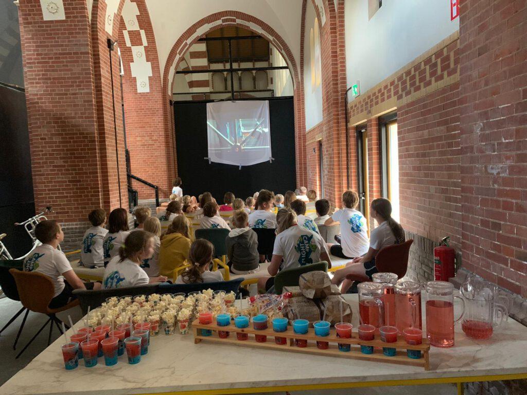 Film kijken in de rijksmonumentale Clemenskerk tijdens Flight Camp bij Flight Deck 53 trampolinepark in Hilversum